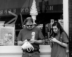 Communication - Father & Daughter (photo_secessionist) Tags: communication communicating fatherdaughter cellphone ignoringeachother street pentax mesuper soligorf35452880mmzoommacrolens film 35mm blackwhite bw bn ilford selfdevelped kodak d76 hp5