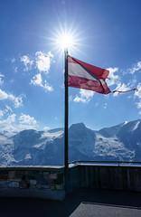 Flagge Österreichs (KaAuenwasser) Tags: flaggeösterreichs edelweisspitze grosglocknerhochalpenstrase flagge fahne sonne sonnenstern berggipfel alpen schnee eis landschaft stern strahlen licht himmel blau wolken berge gipfel wind wetter frühsommer juni 2019 sony ilce7rm3 schatten