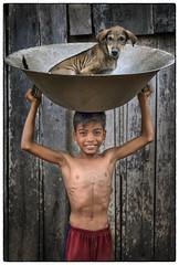 Cambodia, Kratie - Puppy and boy (Mio Cade) Tags: cambodia kratie ricewhiskey whiskey rice boy puppy dog kid child pet friend pot fun portrait documentary reportage asia mediumformat