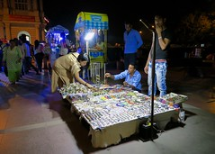 Street Vendor at Night (Mondmann) Tags: streetvendor delhi india connaughtplace jewelry jewelryvendor candid street streetphotography night nighttime outdoors southasia people shopping indians mondmann canonpowershotg7x travel travelphotography