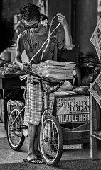 Paperboy (FotoGrazio) Tags: bicycle travelphotography fotograzio delivery streetphotography newspapers paperboy waynesgrazio streetscene streetvendor socialdocumentaryphotography culture makingaliving parttimejob philippines bacolod tying sandles vendor street waynestevengrazio sunglasses travel feet streetportrait filipino pacificislander business work visayas lifeinthephilippines waynegrazio