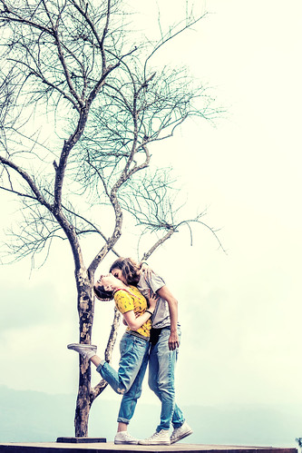 A view of a loving couple posing on the beautiful white sky backgorund on th cliff. Bali island.