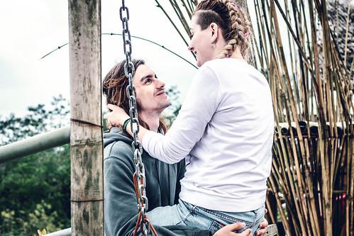 Young honeymoon couple swings in the jungle near the lake, Bali island, Indonesia.