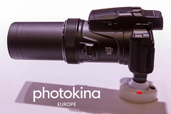 "Camera with 125x optical zoom wide 4k next to picture Titel ""photokina Europe"" (verchmarco) Tags: 2018 cologne kölnmesse köln messe photography photokina noperson keineperson isolated isoliert electronics elektronik lens linse contemporary zeitgemäs machinery maschinen plastic kunststoff power leistung optometry optometrie technology technologie equipment ausrüstung steel stehlen portable tragbar eyesight sehvermögen glazed glasiert appliance gerät classic klassisch zoom zoomen graphicdesign grafikdesign average durchschnittlich2019 2020 2021 2022 2023 2024 2025 2026 2027 2028 2029 2030 spain nikkor farm camera pet macromondays cielo decoration day eos"