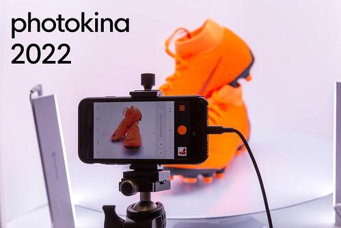 Smartphone auf einem Stativ, mit geöffneter Fotoapparat für Produktfotografie und dem Bildtitel