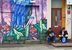 Bad news ? (f22photographie) Tags: streetscene streetphotography colourful people expressions sad mobilephone sittingdown pavement wall mural streetart camdentown london