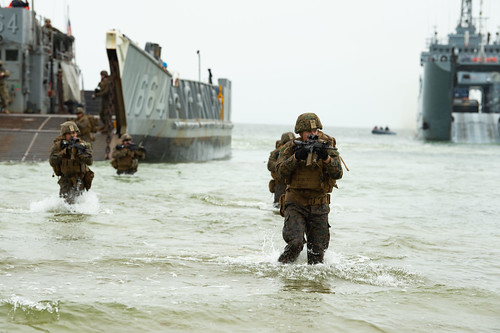 U.S. Marines wade ashore from a landing craft, utility during an amphibious assault for exercise Baltic Operations (BALTOPS) 2019.