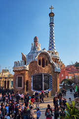 March 2017, Barcelona, Spain - Administration office at the entrance of the Park Guell. Building with pinnacle and five-pointed cross designed by Antoni Gaudi with a crowd of tourists around. (Midoritai) Tags: administration office entrance park guell building pinnacle fivepointed cross designed antoni gaudi crowd tourists people tourism peak top tower mosaic casa barcelona house landmark spain catalonia gingerbread attraction trencadis technique art architecture facade modern modernism artist travel famous broken pottery tile orange summer unusual masterpiece sunny pavilion design guel bureau