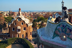 March 2017, Barcelona, Spain - View from the mosaic Serpentine bench of the Park Guell to the Casa del Guarda gatehouse and panorama of the city. (Midoritai) Tags: view mosaic serpentine bench park guell casa guarda gatehouse panorama barcelona city central terrace guel height sea dusk gingerbread house building antonio gaudi modernism roof tourists people landmark tourism spain attraction entrance trencadis art architecture modern artist travel famous broken tile masterpiece spring sunny design ceramic creature head artwork museum