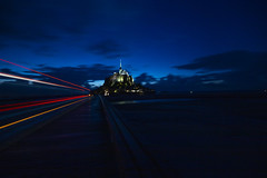 """as sight fails in the onrushing night the last bus ghosts past to collect the last load from Mont Saint Michel, Manche, Normandie, France (grumpybaldprof) Tags: canon 70d """"canon70d"""" sigma 1020 1020mm f456 """"sigma1020mmf456dchsm"""" """"wideangle"""" ultrawide """"fineart"""" ethereal striking artistic interpretation impressionist stylistic style contrast shadow bright dark black illuminated mood moody atmosphere atmospheric """"longexposure"""" night nocturne nighttime """"lowlight"""" """"montstmichel"""" """"stmichael'smount"""" avranches manche normandy france tidal island sea abbey """"bayeuxtapestry"""" monastery """"8thcentury"""" unesco """"worldheritagesite"""" fortifications """"quicksand"""" castle bus lights headlights sky clouds"""