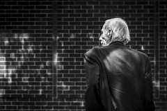 The Brick Wall (Leanne Boulton) Tags: urban street candid portrait portraiture streetphotography candidstreetphotography candidportrait streetportrait streetlife old elderly man male face expression emotion mood atmosphere brick wall dappled sunlight jacket hair wrinkles lines tone texture detail depthoffield bokeh naturallight outdoor light shade shadow city scene human life living humanity society culture lifestyle people canon canon5dmkiii 70mm ef2470mmf28liiusm black white blackwhite bw mono blackandwhite monochrome glasgow scotland uk