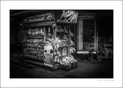 San José fruit stand (G. Postlethwaite esq.) Tags: canon40d canonefs1785mmkitlens costarica sanjosé centralamerica corner esquina fruitstand photoborder pineapples rincon shop streetscene woman