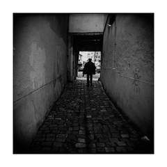 (Oeil de chat) Tags: nb bw monochrome film pellicule argentique mf 120 moyenformat mediumformat carré lomography holga 120n kodak trix rodinal streetphoto photoderue silhouette ambiance pavés sombre