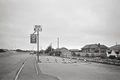 Bodelwyddan, August 1995 (Paul of Congleton) Tags: bodelwyddan denbighshire wales uk road pub publichouse sign evening houses 35mm monochrome blackandwhite film