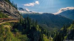 Take A Train (Robert Streithorst) Tags: alaska clouds landscape mountains peaks railroad rays robertstreithorst rock scenic snow snowcap train trees whitepass wilderness