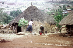 78-644 (ndpa / s. lundeen, archivist) Tags: nick dewolf color photograph photographbynickdewolf 1976 1970s film 35mm 78 reel78 africa northernafrica northeastafrica african ethiopia southernethiopia ethiopian people localpeople village unidentified unidentifiedvillage onfoot walking buildings houses homes building house home hut huts thatchroof thatchedroof road street dirtroad sheetmetalroof terrain landscape hill hillside trees woman women localwoman localwomen headcovering scarf children kids youngwoman youngwomen mother pedestrian
