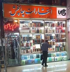 A shopper browsing at a mall entirely made up of bookshops in Enghelab Street, Tehran, Iran (Asa Cusack) Tags: iran tehran books bookshops
