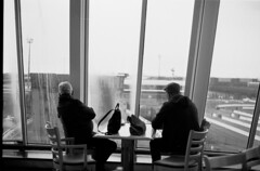 The husbands (Elios.k) Tags: horizontal indoors interior boat ferry people twomen sitting table lookingoutthewindow window rain rainyweather port atsea dunkirkport ferryterminal buildings departure café dof depthoffield focusonforeground backgroundblur blackandwhite bw mono monochrome travel travelling march 2018 vacation canon camera photography englishchannel dunkirk dunkerque france europe film analoguephotography scannedfilm agfaapx100 analogfilm grain contrast canona1 a1 analogcamera