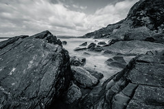 On the rocks [ Explore ] (NikNak Allen) Tags: bovisand plymouth devon beach rock stones sea water waterscape landscape seascape tide shore shoreline sky clouds grey black white blackandwhite longexposure smooth dramatic coast cliff