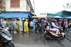 Chinese tourists queue up to enter the busy market (shankar s.) Tags: seasia thailand bangkok krungthepmahanakhon krungthep bangkoksuburbs outskirtsofbangkok maeklongrailway localmarket localcommerce riversideshopping touristattraction runningrightthroughthemarket dangerouslyclose localproduce fruitandvegetablemarket wetmarket maeklong maeklongtrainmarket maeklongrailwaymarket talatromhup umbrellapulldownmarket exotic safetyhazard railwaystation trainstation srt staterailwaysofthailand dieselrailcartrain dieselmultipleunit dmu queue lineup chinesetourists exasperating