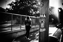 Amor and rider. (LACPIXEL) Tags: amor ridder femme woman mujer contrejour backlit rue street calle barrière fences grille rejas noiretblanc blancoynegro blackwhite sony marcher andar walk walking autocollant sticker poteau lampadaire farol streetlight flickr streetphotographer photographederue lacpixel