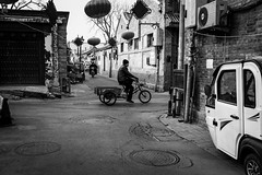Passing-by (Go-tea 郭天) Tags: pékin républiquepopulairedechine beijing hutong old ancient narrow alley history historical historic traditional tradition building cny decoration festival cold winter quiet quietness calm empty desert bicycles bikes man ridding ride rider movement sun sunny shadow motorbike motorcycle men hat manholes electricity electric lines bricks pavement street urban city outside outdoor people candid bw bnw black white blackwhite blackandwhite monochrome naturallight natural light asia asian china chinese canon eos 100d 24mm prime