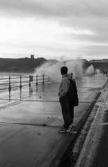 Say Hello, Wave Goodbye (Mano Green) Tags: people sea seafront promenade waves castle street road sky water splash crash scarborough north yorkshire england uk summer september 2016 canon eos 300 40mm lens ilford hp5 400 35mm film black white ilfosol s epson perfection v550 portrait light shadow
