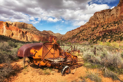Rusting (KPortin) Tags: rustyandcrusty capitolreefnationalpark farmequipment cliffs clouds sagebrush