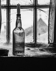 Dusty window (squirrel.boyd) Tags: bottle candle decay spiderweb webs dust windows reflections