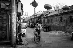 Old fashioned (Go-tea 郭天) Tags: pékin républiquepopulairedechine beijing hutong ancient old narrow alley history historical historic traditional tradition buildings bricks pavement cny man worker uniform movement bicycle bike ride riding rider smoke smoking cigarette cold winter sun sunny shadow street urban city outside outdoor people candid bw bnw black white blackwhite blackandwhite monochrome naturallight natural light asia asian china chinese canon eos 100d 24mm prime alone lonely empty portrait
