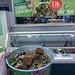 Hand hält einen Salatmix in der grünen To-Go-Salatschüssel, vor der Angebotstafel der digitalen PicaDeli Salatbar