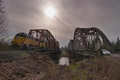 Backlit Bridge Duo (SeanFKelly) Tags: backlit oregon willamette valley train railroad sun bridge bridges arch up unionpacific river water grass weeds sky contrail overcast cloudy moody