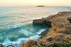 The entrance to spouting horn (Lostinplace) Tags: sunset surf longexposure ocean oregon otterrock newport fence headland sandstone
