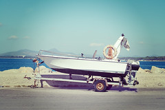 boat on a trailer by the dock (sophia.alachouzos) Tags: trailer boat vintage retro old style cruise delivery white travel swimming yacht modern rest blue transportation water device comfortable asphalt road street port harbor dock quay wharf effect italy
