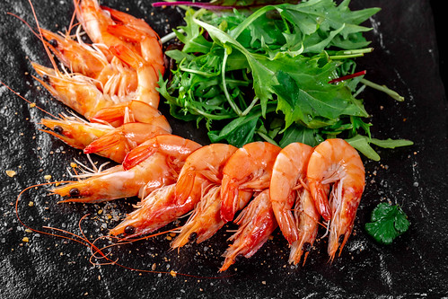 King prawns with fresh arugula leaves on black background