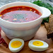 Bowl of beetroot soup borsch with egg, pepper and slices of black bread
