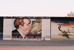 a gentle peck - East Side Gallery (viktor.rpprt) Tags: berlin film filmphotography filmisalive thefilmcommunity thefilmgang kodakfilm shootfilm shotonfilm grain ishootfilm vintagecamera analog canona1 kodak iso200 longexposure dawn berlinermauer dmitrivrubel marcengel mural brezhnev honecker kiss soviet berlinwall
