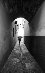 (cherco) Tags: woman architecture light rain tunnel blackandwhite blancoynegro granada spain silhouette solitary solitario silueta shadow street sombra shadows composition canon composicion city ciudad urban umbrella lonely luz alone arch monochrome