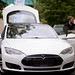 Autoverkäufer führt den Tesla Model S einem potentiellen Käufer vor