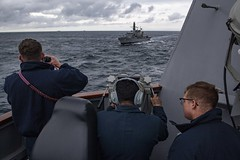 Sailors watch from aboard USS Michael Murphy (DDG 112) as a Chilean navy frigate passes alongside.