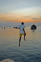Jumping for the horizon - Stonetown, Zanzibar (TravelsWithDan) Tags: youngman jumping sunset boats water ocean indianocean abouttogetwet city urban candid stonetown zanzibar tanzania africa canong3x