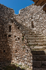 Ruined windmill interior (Peter.Luty) Tags: kioni ionianislands greece ionian islands stones stone windmill ruin ruined isolated rough wall stark dramatic romantic ithaca natural stairs steps windows niches bluesky