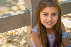 Sitting Against the Fence (Kevin MG) Tags: portrait park kids child childhood adolescent schoolage outdoor girl smile teeth portfolio