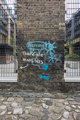 Warning (Spannarama) Tags: river thames deptford greenwich london uk graffiti watergatestreet warning monsters cobbles cobblestones bricks wall flats