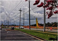 Landscape with Utility Wires   Powers Ferry Road Marietta, GA (steveartist) Tags: clouds utilitypoles utilitywires constructionsite parkinglot grass crepemyrtle jeepcherokee safetybarrels penantsigns sonydscwx220 snapseed photostevefrenkel