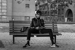 Interrupted (Silver Machine) Tags: london streetphotography street streetportrait candid candideyecontact man sitting bench earplugs adidas trainers monochrome mono blackwhite bw fujifilm fujifilmxt3 fujinonxf35mmf2rwr