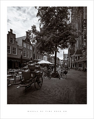 Wheels of time move on (Parallax Corporation) Tags: haarlem grotekerkofstbavohaarlem sonya7rii zeissbatisfe18mmf28 markt blackwhite monochrome milkchurn milkcart restaurants parasol netherlands wideangle trees