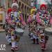Karnevalisten laufen in Clownskostüm durch die Fußgängerzone und trommeln neben dem Bildtitel