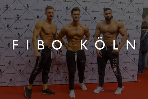 Drei sportliche Männer mit nacktem Oberkörper zeigen ihre Muskeln und Sixpacks auf dem roten Teppich, mit dem Bildtitel