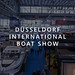 "Visitors in an exhibition hall with many luxury yachts and boats, with the picture title ""Düsseldorf International Boat Show"""